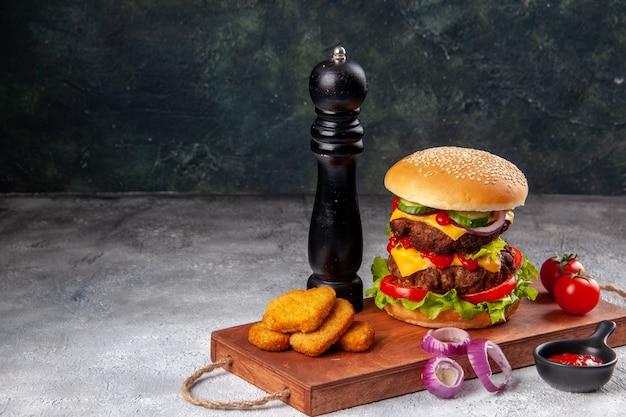 Panino gustoso fatto in casa e pomodori pepite di pollo cipolle pepe su tagliere di legno ketchup sul lato sinistro su superficie sfocata