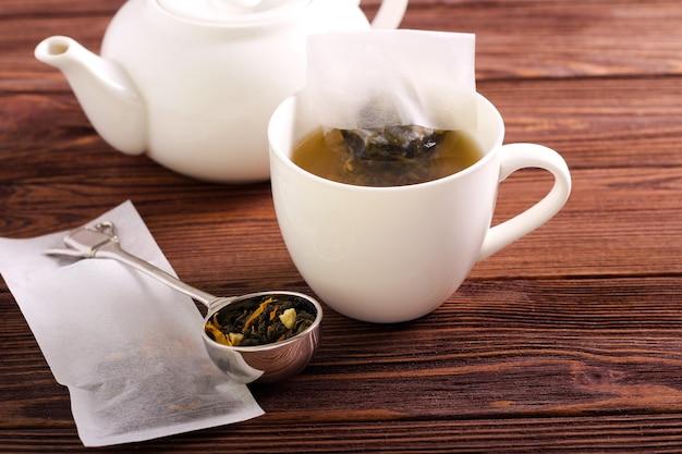 Preparato di tè fatto in casa in bustine di tè, su sfondo di legno