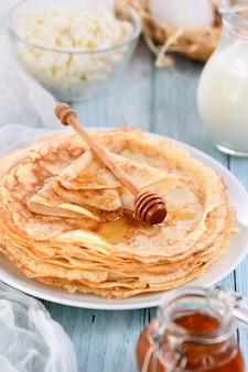 Frittelle di crepe sottili fatte in casa con miele impilate in una pila su un tavolo con una pentola di latte