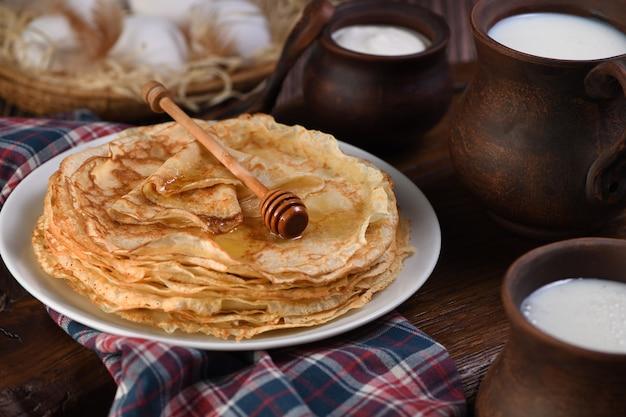 Pancake sottili fatti in casa con miele impilati in una pila su un tavolo di legno con una tazza di latte