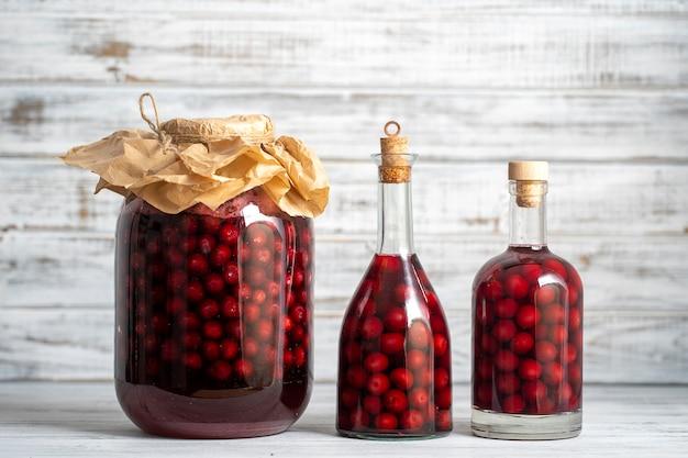 Tintura artigianale di ciliegia rossa. berry bevande alcoliche concetto. vino rosso fatto in casa a base di ciliegie mature in vasi e bottiglie di vetro