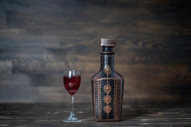 Tintura casalinga di ciliegia rossa in bottiglie decorative e un bicchiere di vino su legno