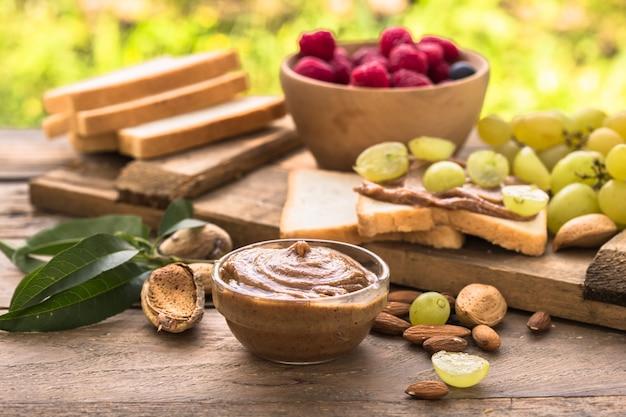 Pane tostato fatto in casa con burro di mandorle e uva sul tavolo di legno per la colazione. delizioso pane tostato pronto da servire. pane tostato con crema spalmabile per colazione