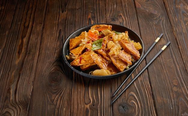 Il tofu fatto in casa soffriggere con le verdure in salsa dolce calda e un paio di bacchette sul tavolo in legno scuro e lo spazio della copia. vista dall'alto del concetto di cibo asiatico