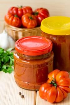 Salsa piccante di pomodoro fatta in casa con aglio e pepe in barattoli di vetro sulla tavola di legno.
