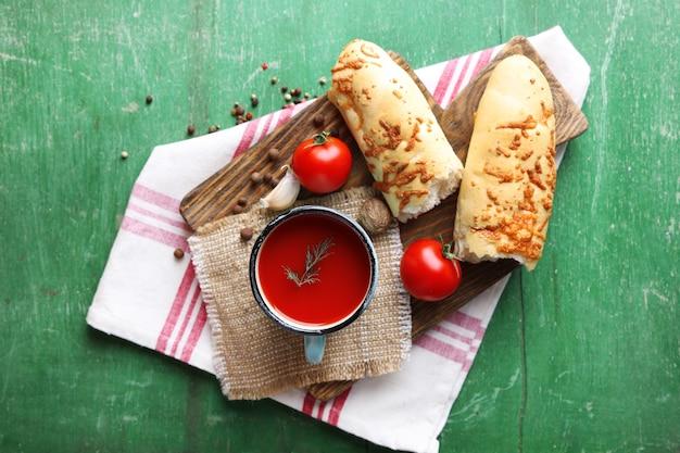 Succo di pomodoro fatto in casa in tazza, spezie e pomodori freschi su un tavolo di legno