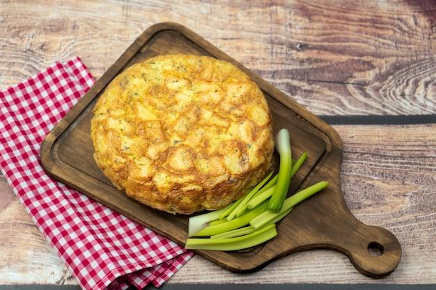 In casa tortilla de papas o frittata di patate su una tavola di legno su un tavolo rustico. cucina spagnola naturale e tipica. concetto di cucina regionale ed etnica.