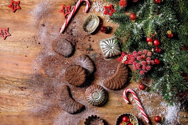 Fatti in casa tradizionali biscotti di pasta frolla di natale mezzelune al cioccolato con zucchero a velo di cacao in piatto di ceramica con stampi per biscotti, abete, decorazioni di stelle di natale rosse su fondo in legno
