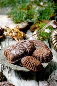 Fatti in casa tradizionali biscotti di pasta frolla di natale mezzelune di cioccolato con zucchero a velo di cacao in piatto di ceramica con stampi per biscotti, abete, decorazioni di stelle di natale su fondo in legno