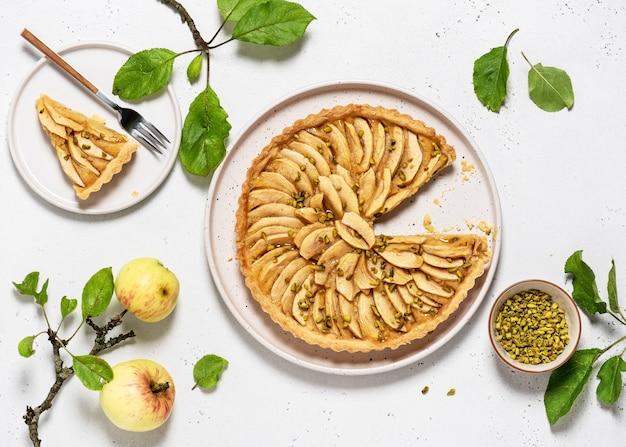 Crostata di mele al forno tradizionale francese fatta in casa con ripieno di crema pasticcera e pistacchi verdi