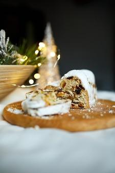 Stollen di natale di marzapane tradizionale fatto in casa su sfondo bianco, con luci e decorazioni natalizie