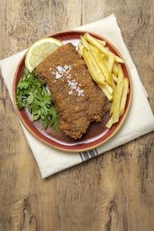 Scaloppa di vitello milanese tradizionale fatta in casa con patatine fritte, insalata, salsa alla maionese