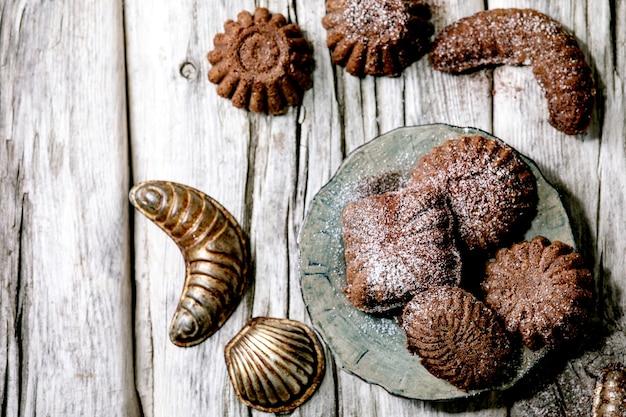 Biscotti di pasta frolla tradizionali fatti in casa mezzelune al cioccolato con zucchero a velo di cacao in piatto di ceramica con stampi per biscotti su fondo in legno vecchio