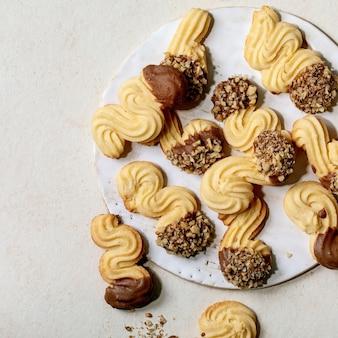 Biscotti di pasta frolla tradizionali fatti in casa di forme diverse con glassa al cioccolato e noci sul piatto di ceramica su sfondo bianco. lay piatto, copia spazio. immagine quadrata