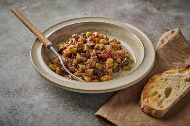 Caponata tradizionale siciliana fatta in casa con melanzane, zucchine, pomodori, olive e ciabatta. primo piano, copia spazio