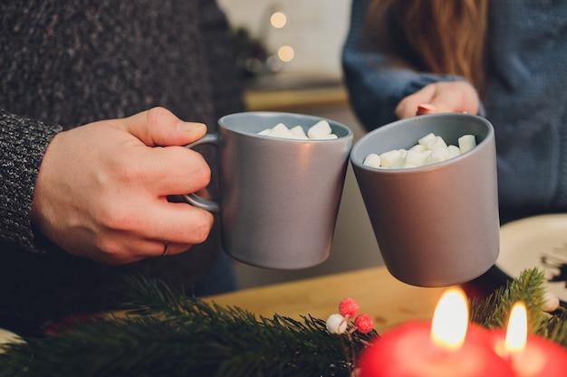 Due bicchieri di cacao fatti in casa con marshmallow. bevanda calda invernale sul fondale in legno decorato con bastoncini di cinamon e rami di abete.