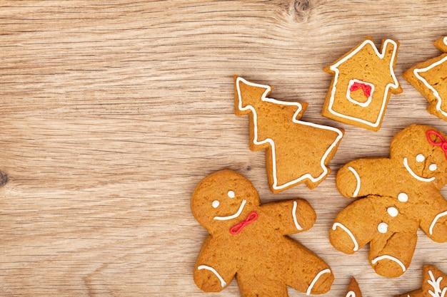 Vari biscotti fatti in casa del pan di zenzero di natale su fondo di legno con lo spazio della copia