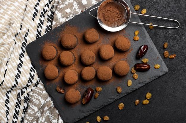 Tartufi vegani fatti in casa con frutta secca, noci e polvere di cacao crudo servito su lastra di ardesia nera