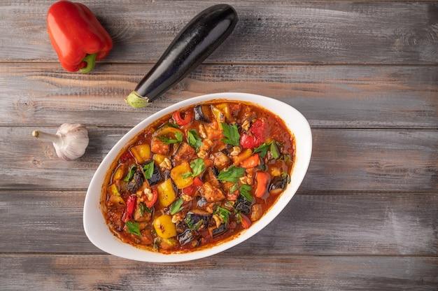Stufato di verdure fatto in casa di melanzane, zucchine, pomodori, peperoni, aglio, prugne e verdure sulla ciotola