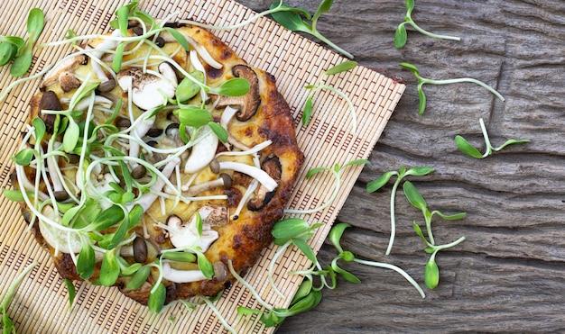 Pizza vegetariana fatta in casa con germogli di girasole su uno sfondo di tavolo in legno