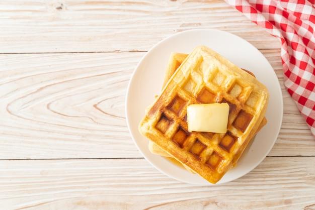 Pila di waffle fatti in casa con burro e miele o sciroppo d'acero