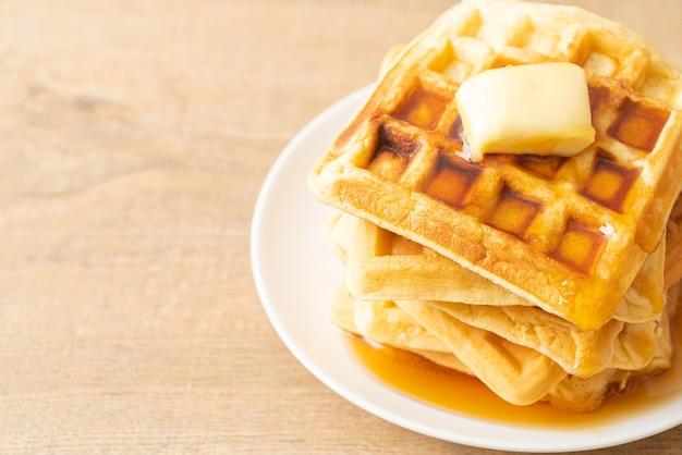 Pila di waffle fatti in casa con burro e miele o sciroppo d'acero Foto Premium