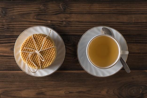 Cialde fatte in casa e tè con cannella e limone su un tavolo di legno. disposizione piatta. torte fatte in casa con tè.