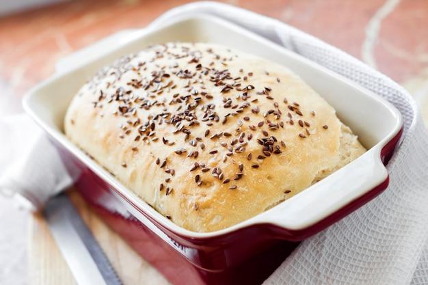 Pane di grano fatto in casa con semi di lino in teglia in ceramica rossa