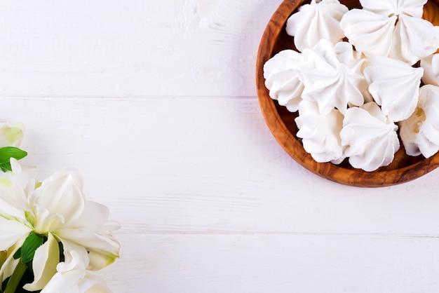 Meringa bianca fatta in casa nel piatto di legno sulla superficie di legno bianca