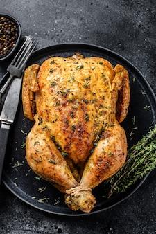 Girarrosto intero di pollo al forno fatto in casa con timo. sfondo nero. vista dall'alto.
