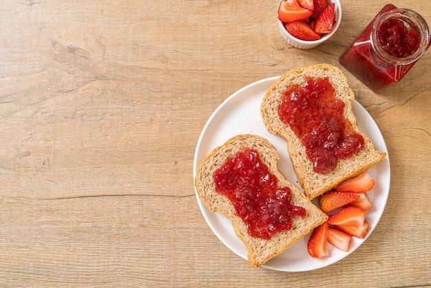 Pane integrale fatto in casa con marmellata di fragole e fragole fresche