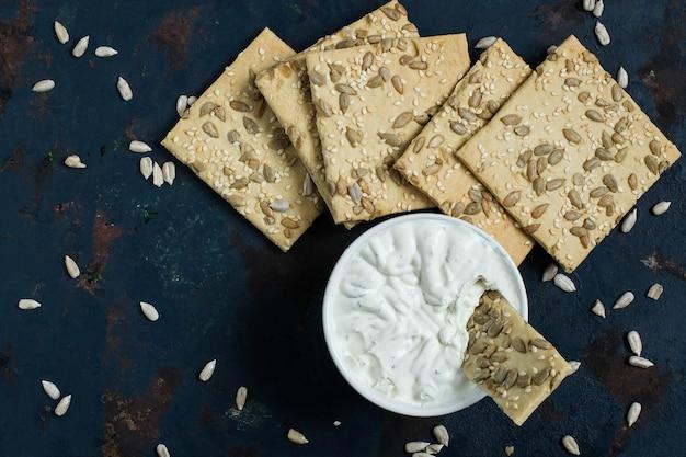Crackers integrali fatti in casa con semi di girasole al sesamo e crema di formaggio