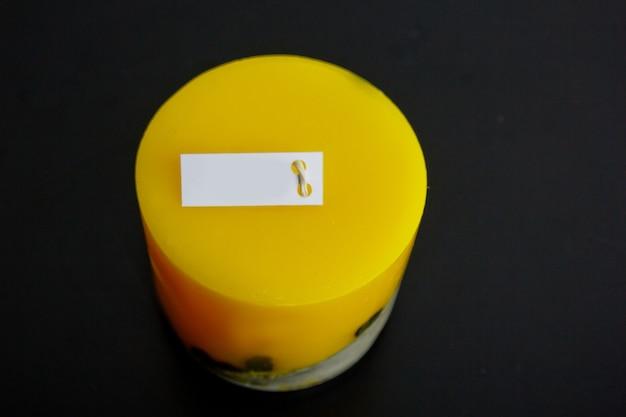 Candela gialla fatta in casa con cemento su una superficie nera