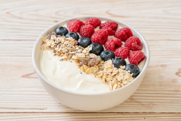Ciotola di yogurt fatto in casa con lamponi, mirtilli e muesli - stile di cibo sano