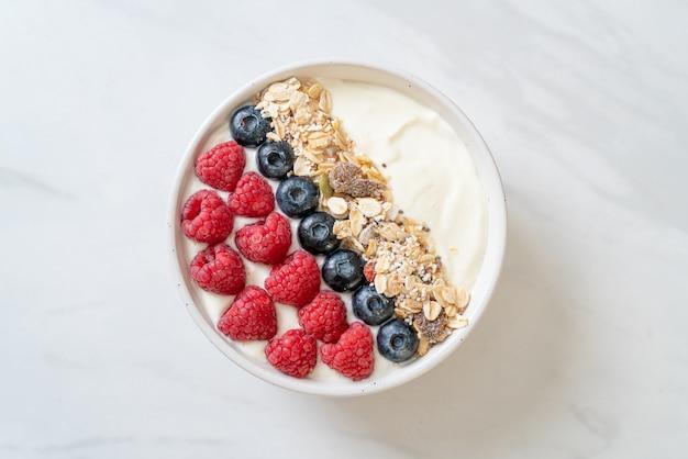 Ciotola di yogurt fatto in casa con lamponi, mirtilli e muesli. stile di cibo sano