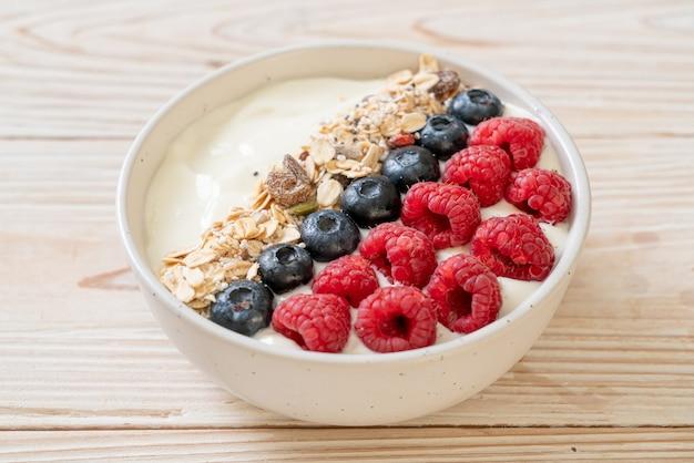 Ciotola di yogurt fatta in casa con lampone, mirtillo e muesli - stile alimentare sano