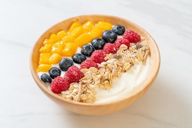 Ciotola di yogurt fatto in casa con lamponi, mirtilli, mango e muesli - stile di cibo sano