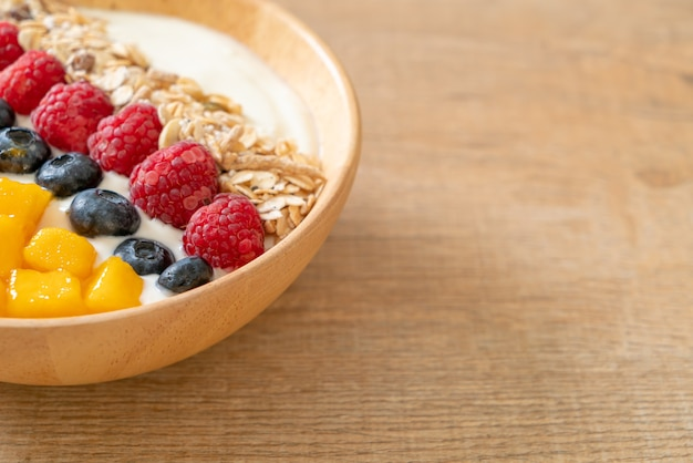 Ciotola di yogurt fatta in casa con lampone, mirtillo, mango e muesli. stile alimentare sano