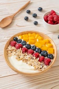 Ciotola di yogurt fatto in casa con lamponi, mirtilli, mango e muesli