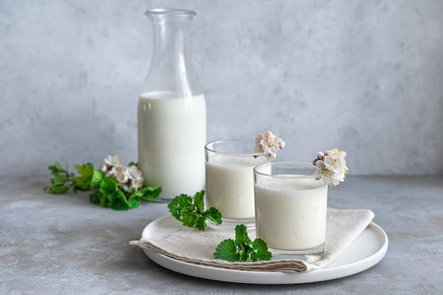 Bevanda allo yogurt fatta in casa: ayran, kefir, lassi, su un muro grigio. bevanda fresca rinfrescante estiva salutare. vista laterale, copia dello spazio.