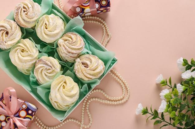 Zephyr fatti in casa o marshmallow in una scatola su una superficie rosa, orientamento orizzontale, vista dall'alto