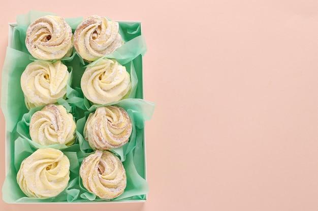 Zephyr o marshmallow fatti in casa in una scatola sul rosa