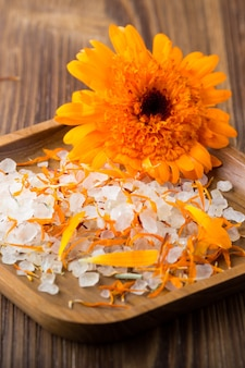 Medicina omeopatica, fiori secchi di calendula e superficie in legno.