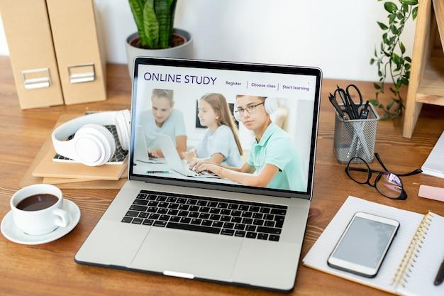 Homepage del sito web educativo sul display del laptop circondato da una tazza di caffè, smartphone e altre forniture