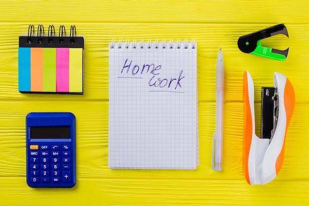 Concetto di compiti a casa disteso. blocchi per appunti con penna, calcolatrice e cucitrice su legno giallo.