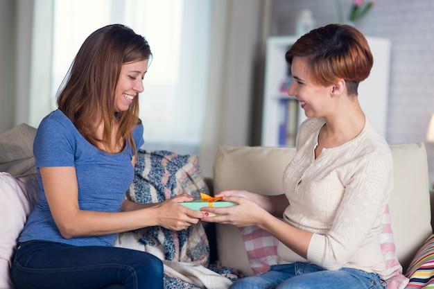 Coppia omosessuale di donne lesbiche a casa sul divano che celebrano una vacanza e regalano scatole con regali