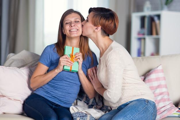 Coppia omosessuale di donne lesbiche a casa sul divano baci sulla guancia celebrando una vacanza e dando scatole con regali