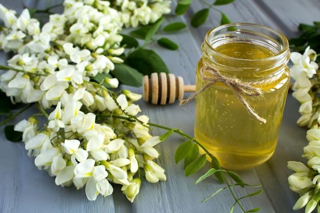Miele e fiori di acacia sul legno grigio