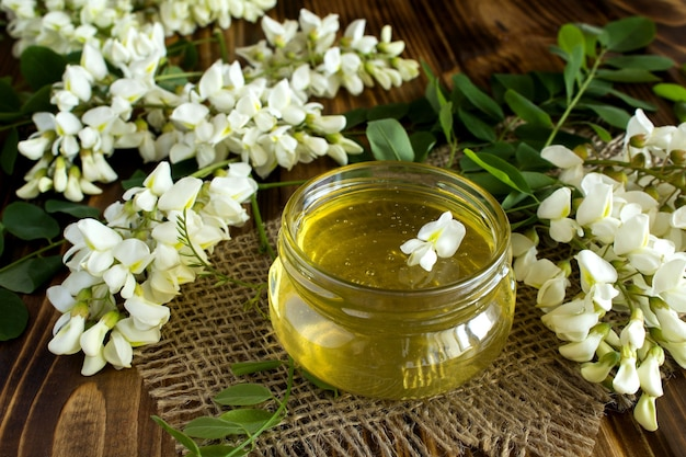Miele e fiori di acacia sullo sfondo di legno rustico