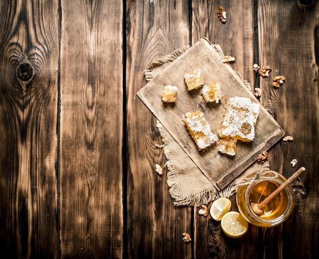 Sfondo di miele miele naturale fette di limone e noci su fondo in legno